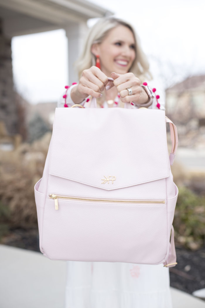 Best Labor Day Sales 2019 by popular Utah fashion blog: image of a woman holding up a blush colored Freshly Picked diaper bag.