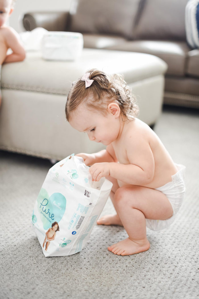 Walmart Baby Registry Must-Have by popular Utah life and style blog, A Slice of Style: image of a little girl wearing only diaper and looking in a package of Pamper's Pure Protection diapers from Walmart