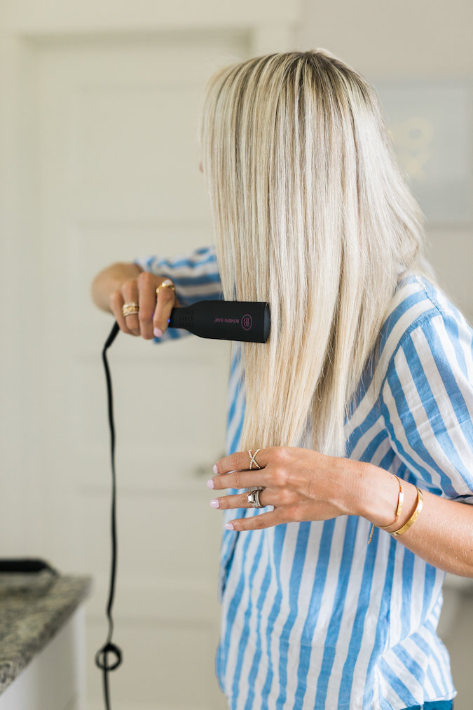 How to Curl Long Hair FAST & Keep your Hair Healthy featured by top Utah beauty blog, A Slice of Style: image of a woman holding hair straighteners