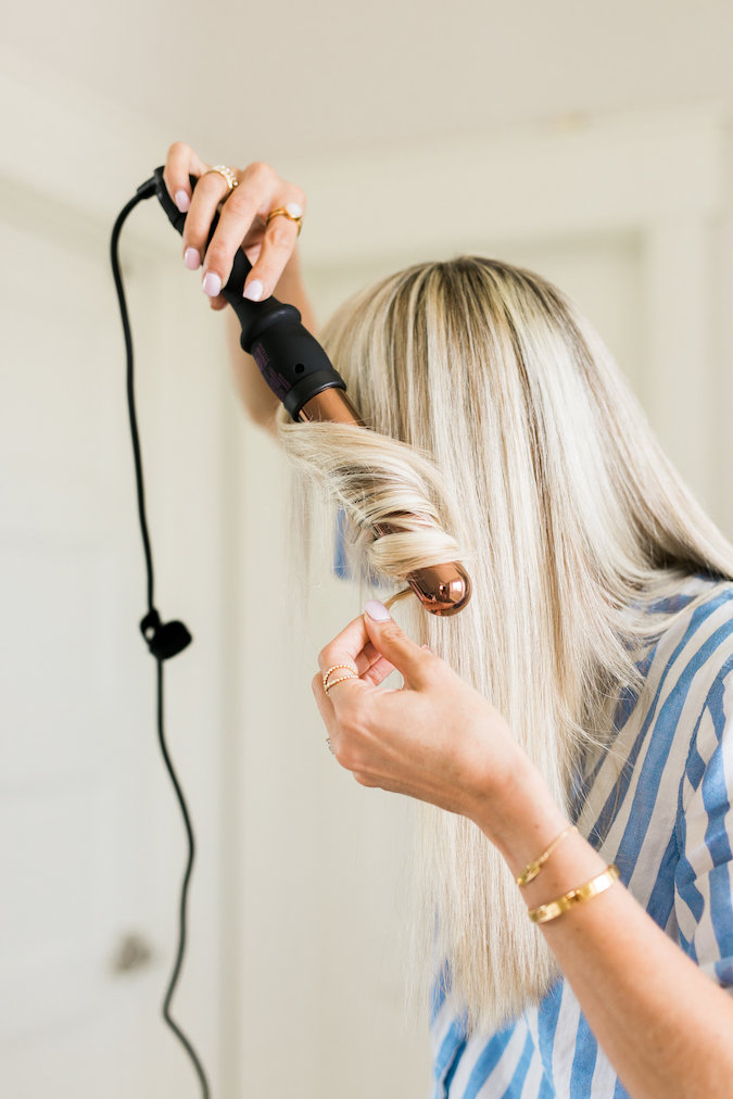 How to Curl Long Hair FAST & Keep your Hair Healthy featured by top Utah beauty blog, A Slice of Style: image of a woman holding a curling wand
