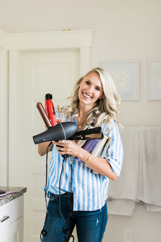How to Curl Long Hair FAST & Keep your Hair Healthy featured by top Utah beauty blog, A Slice of Style: image of a woman holding hair care products to curl her long hair