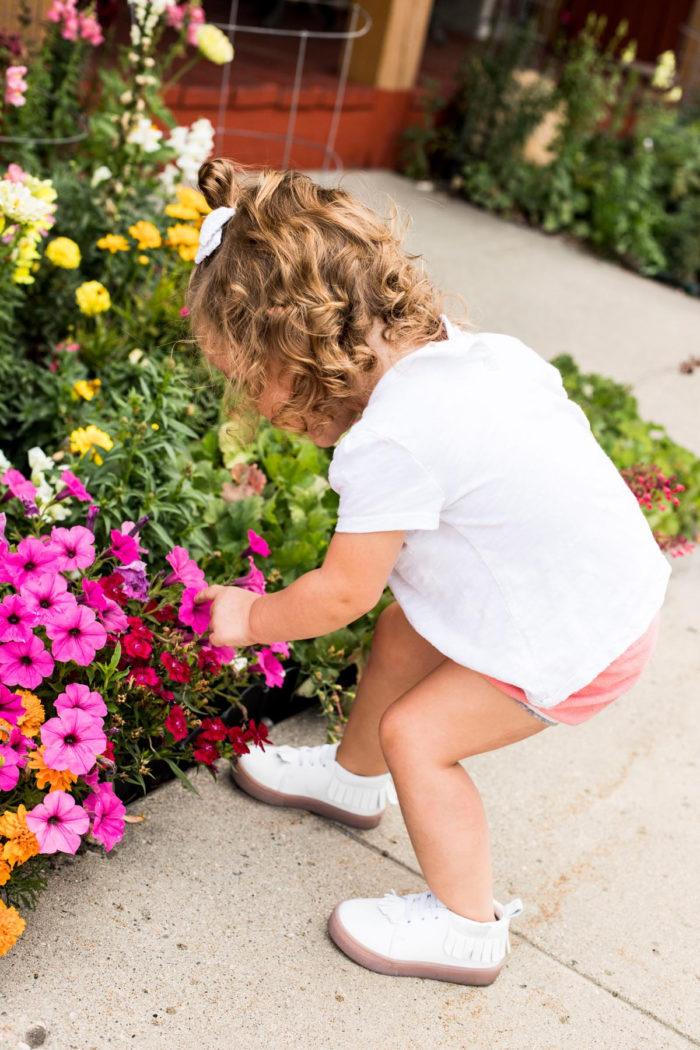 Best Labor Day Sales 2019 by popular Utah fashion blog: image of a little girl bending over to smell some flowers and wearing a pair of white Freshly Picked hard sole sneakers.