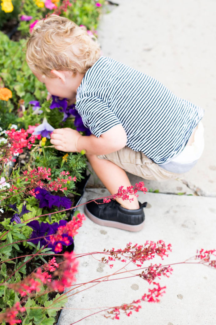 Best Labor Day Sales 2019 by popular Utah fashion blog: image of a little boy bending over to smell some flowers and wearing a pair of black Freshly Picked hard sole shoes.