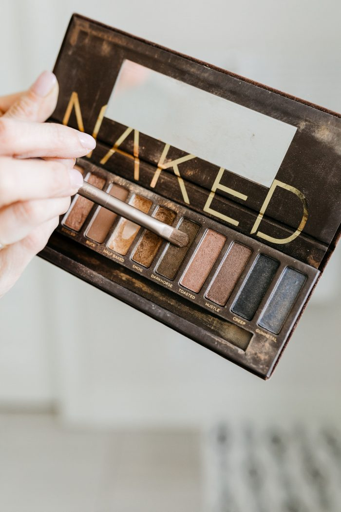 NAKED Palette Tutorial featured by top US beauty blog A Slice of Style; Image of woman in mustard sweater, applying eye shadow.