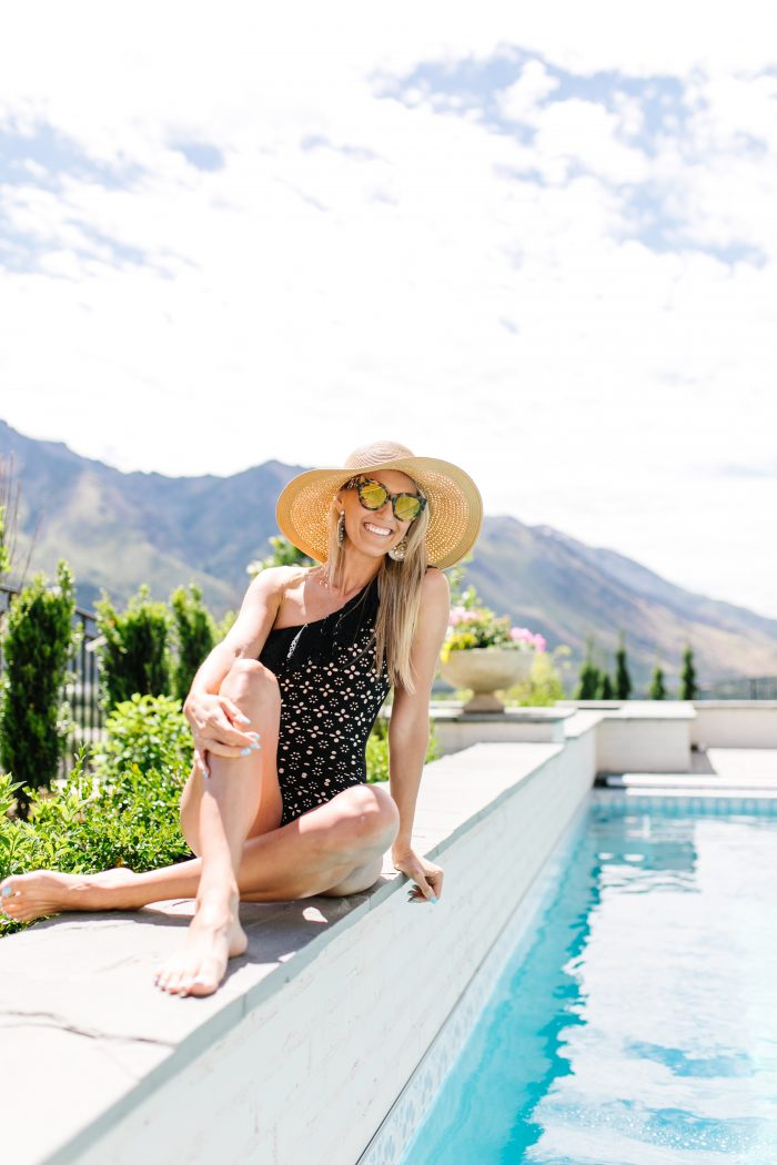 J Crew Summer Style featured by top US life and style blog, A Slice of Style: image of a woman wearing a J crew one piece one shoulder swimsuit, J crew leather sandals, J Crew raffia statement earrings, J Crew straw hat and J Crew oversized sunglasses