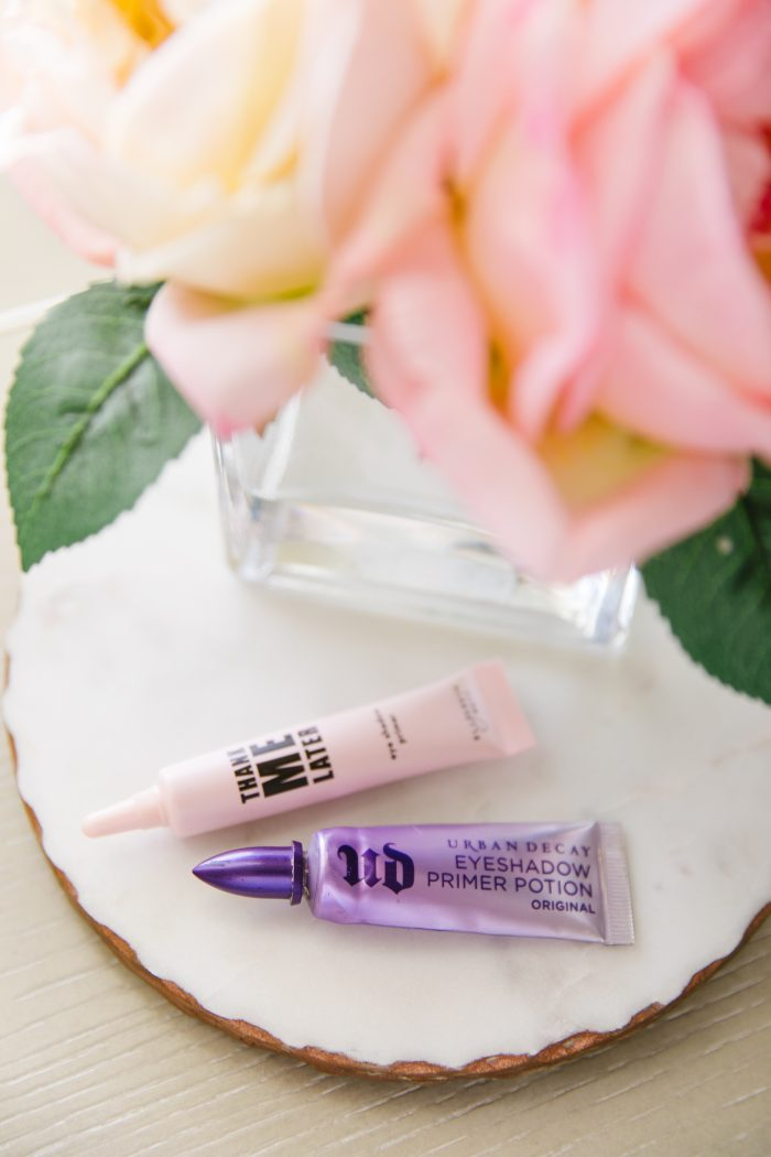 Affordable Amazon Beauty Dupes + Latest Amazon Favorites! by popular Utah beauty blog, A Slice of Style: image of liquid Urban Decay and Thank Me Later liquid eyeshadow next to a small vase of roses.