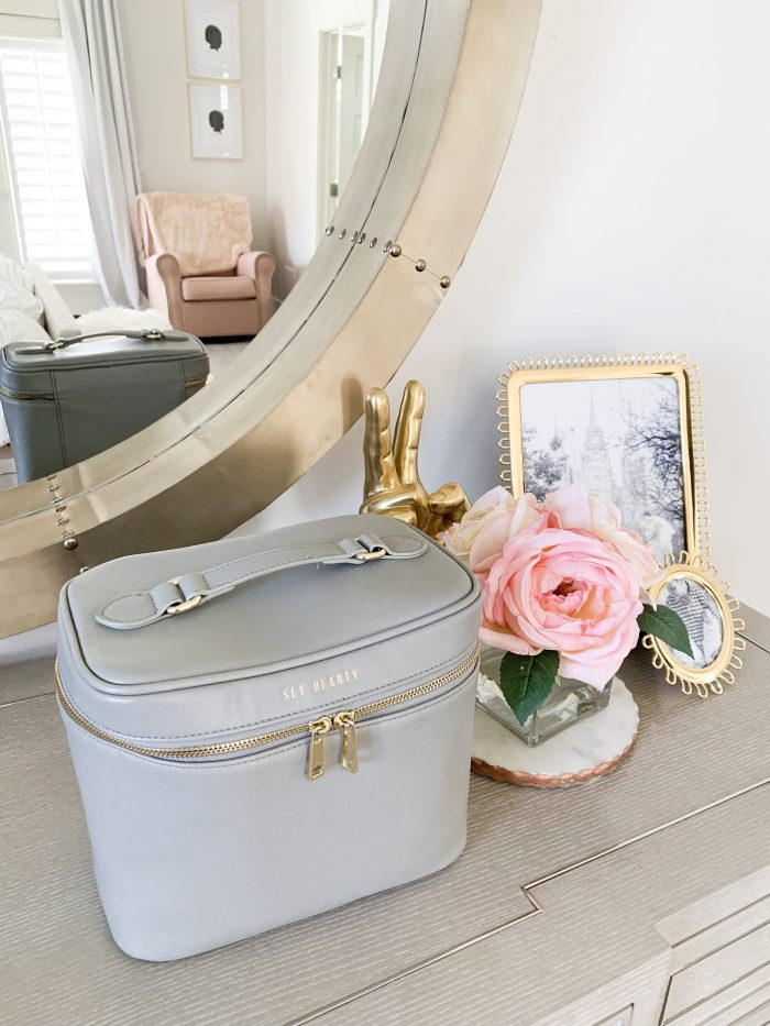 The Only Makeup Bag I'll Ever Need Again!! Sly Beauty Discount Code by popular Utah beauty blog, A Slice of Style: image of a grey Sly Beauty bag on a bedroom dresser.