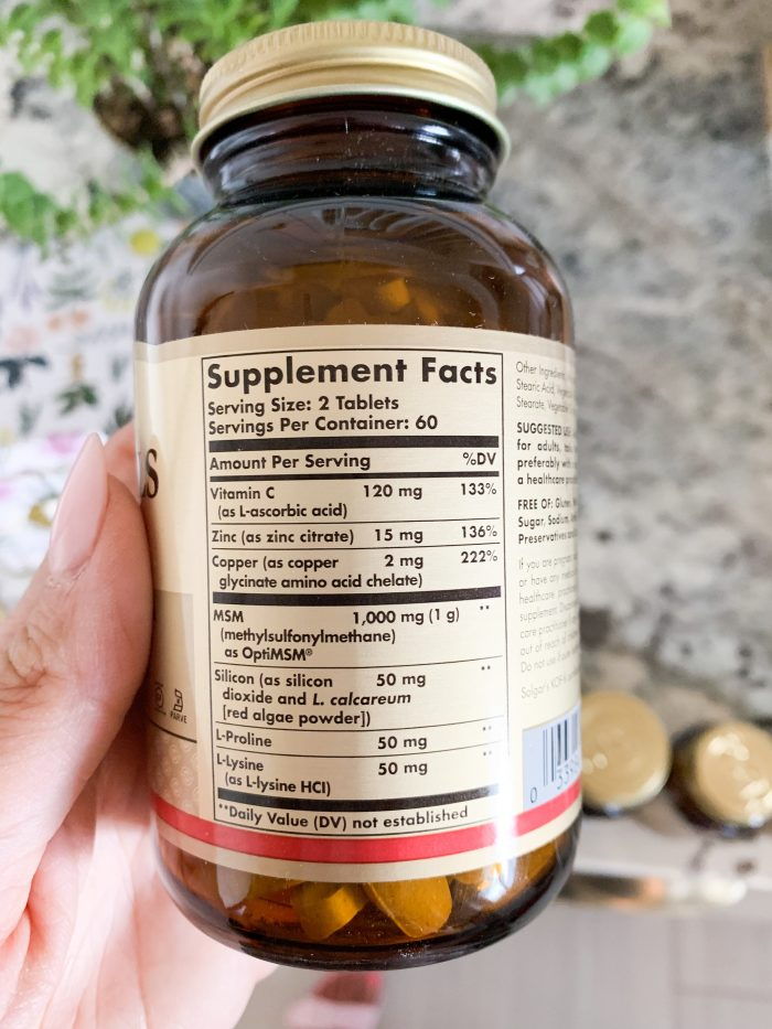 Solgar Vitamins Review + Green Smoothie Recipe by popular Utah life and style blog, A Slice of Style: closeup image of a woman holding a bottle of Solgar Vitamins.