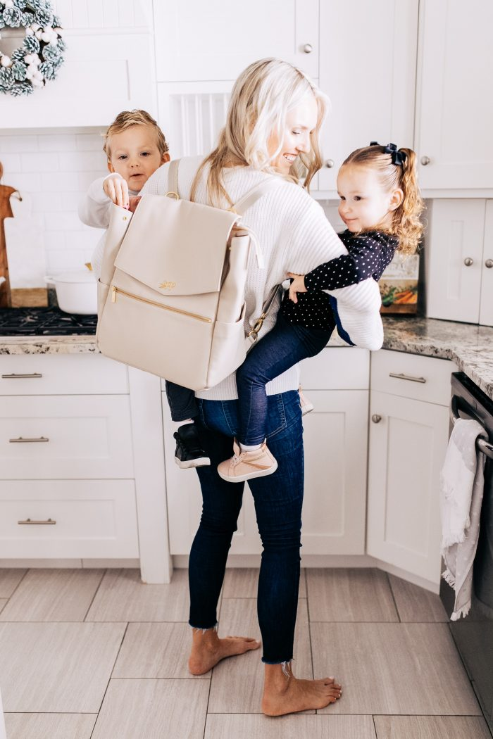 Freshly Picked Coupon Code! by popular Utah fashion blog, A Slice of Style: image of a woman holding her twin kids and wearing a Freshly Picked Diaper bag back pack.