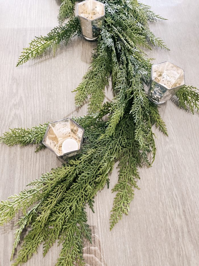 White Christmas decor featured by top US life and style blog, A Slice of Style | My White Christmas Home Decor: Some Items Under $10! by popular Utah lifestyle blog, A Slice of Style: image of a dinning table with a pine bough garland and silver mercury glass candle votives.