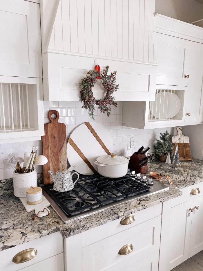 White Christmas decor featured by top US life and style blog, A Slice of Style | My White Christmas Home Decor: Some Items Under $10! by popular Utah lifestyle blog, A Slice of Style: image of a kitchen with a berry Christmas wreath hanging above the stove.