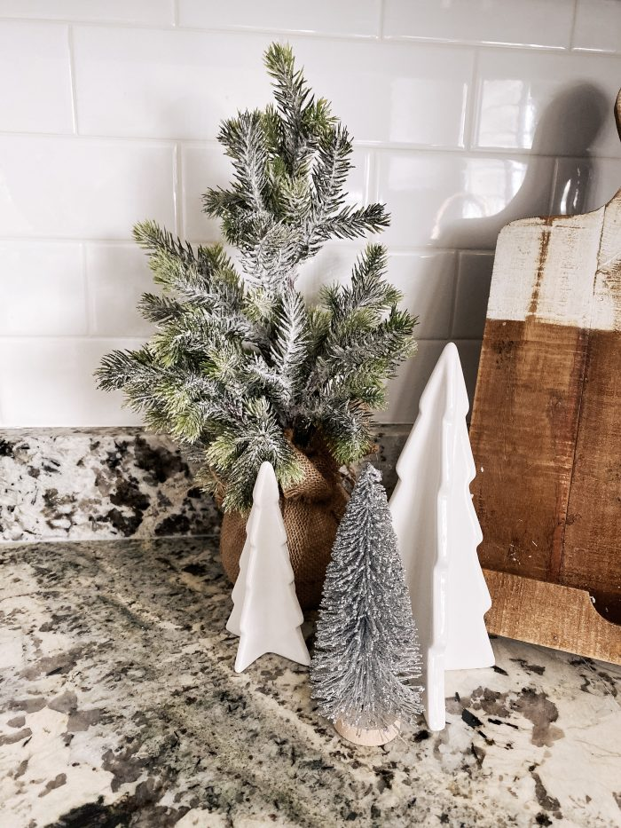White Christmas decor featured by top US life and style blog, A Slice of Style | My White Christmas Home Decor: Some Items Under $10! by popular Utah lifestyle blog, A Slice of Style: image of a kitchen counter with some Target Large Ceramic Christmas Tree Decorative Figurine and mini faux pine trees on it.