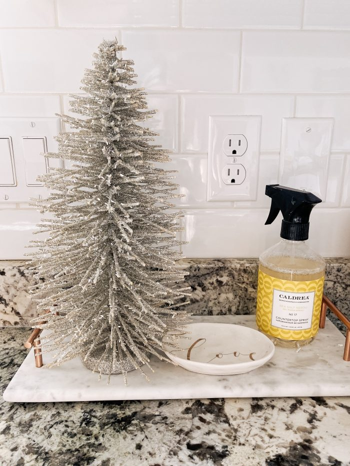 White Christmas decor featured by top US life and style blog, A Slice of Style | My White Christmas Home Decor: Some Items Under $10! by popular Utah lifestyle blog, A Slice of Style: image of a kitchen counter with a mini gold glitter Christmas tree on it.