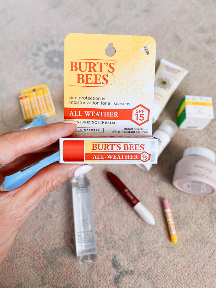 Walmart Beauty Products by popular Utah beauty blog, A Slice of Style: image of a woman holding a Walmart Burt's Bees All-Weather lip balm.