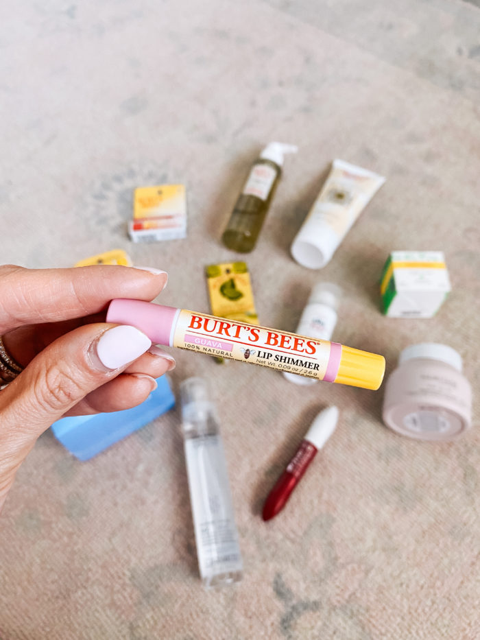 Walmart Beauty Products by popular Utah beauty blog, A Slice of Style: image of a woman holding a Walmart Burt's Bees lip shimmer.