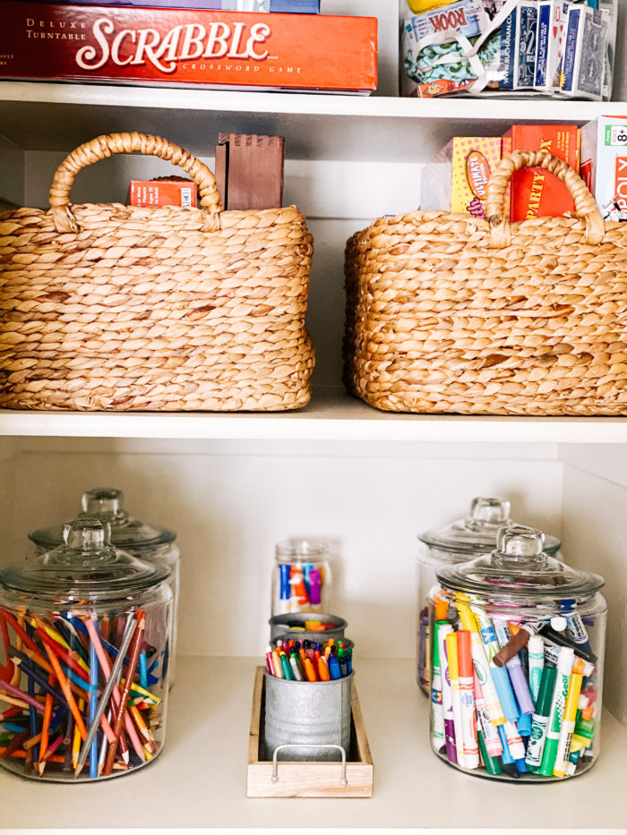 2 Player Games by popular Utah lifestyle blog, A Slice of Style: image of a game closet with woven baskets containing board games, card games, and art supplies.