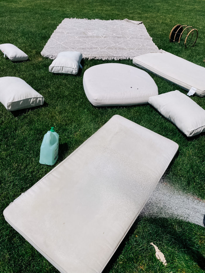 White Outdoor Cushions by popular Utah life and style blog, A Slice of Style: image of a white outdoor cushions and a grey and white outdoor rug spread out on the grass and being sprayed down with a hose.