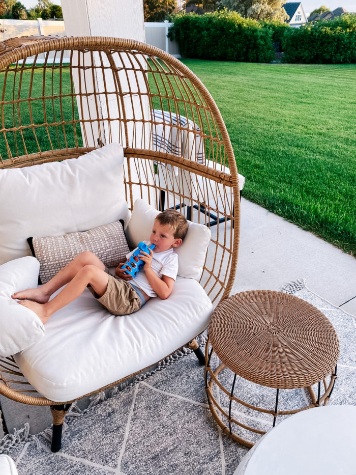 White Outdoor Cushions by popular Utah life and style blog, A Slice of Style: image of a little boy drinking out of a water bottle while he lays down on some white outdoor cushions.