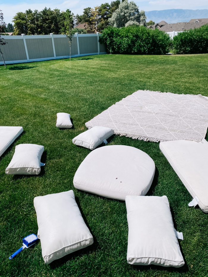 White Outdoor Cushions by popular Utah life and style blog, A Slice of Style: image of a white outdoor cushions and a grey and white outdoor rug spread out on the grass.