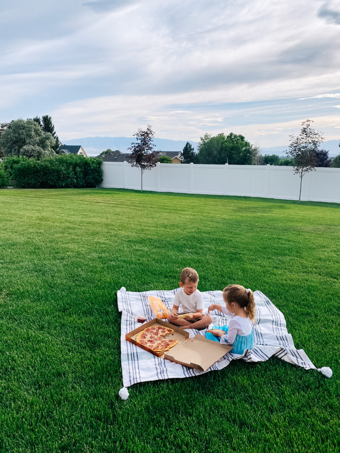 White Outdoor Cushions by popular Utah life and style blog, A Slice of Style: image of two kids eating pizza and sitting on a white and grey stripe blanket in their backyard.