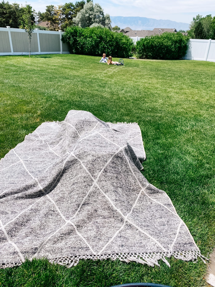 White Outdoor Cushions by popular Utah life and style blog, A Slice of Style: image of a wet grey and white outdoor rug drying on the grass.