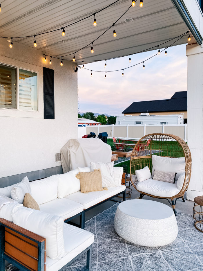 White Outdoor Cushions by popular Utah life and style blog, A Slice of Style: image of a backyard patio with bistro lights, patio furniture and white outdoor cushions.