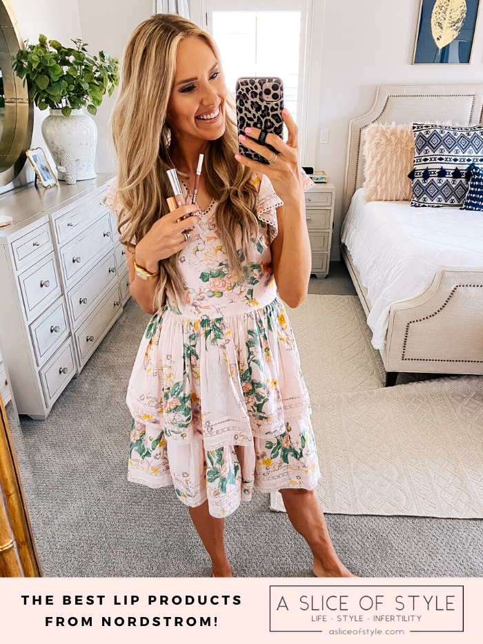 Best Lip Products by popular Utah beauty blog, A Slice of Style: image of Jenica Parcell wearing a pink floral dress and holding a Nordstrom 24/7 Glide-On Lip Pencil URBAN DECAY, Nordstrom Hot Lips Lipstick CHARLOTTE TILBURY, and Nordstrom Full-On™ Plumping Lip Cream BUXOM.