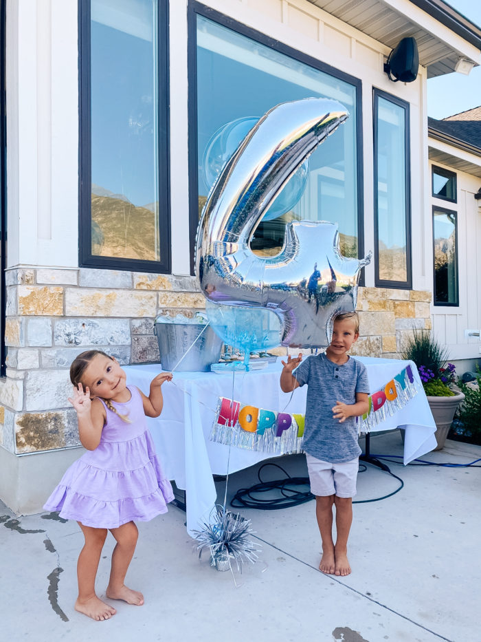 4th Birthday Party by popular Utah motherhood blog, A Slice of Style: image of boy and girl twins holding a birthday balloon bouquet together.