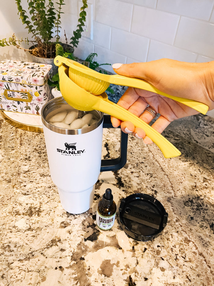 Stanley Travel Mug by popular Utah lifestyle blog, A Slice of Style: image of Jenica Parcell squeezing a lemon into a white Stanley travel mug.