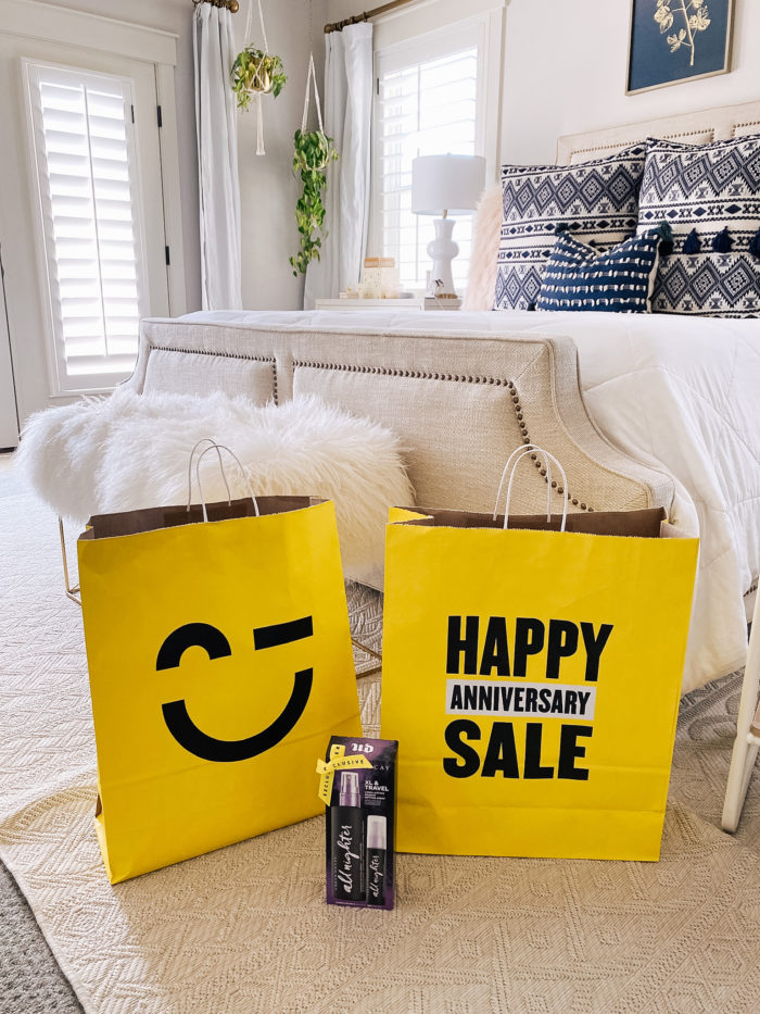 Nordstrom Anniversary Sale by popular Utah beauty blog, A Slice of Style: image of two Nordstrom Anniversary Sale shopping bags resting on the floor in front of a bed and faux fur bench.