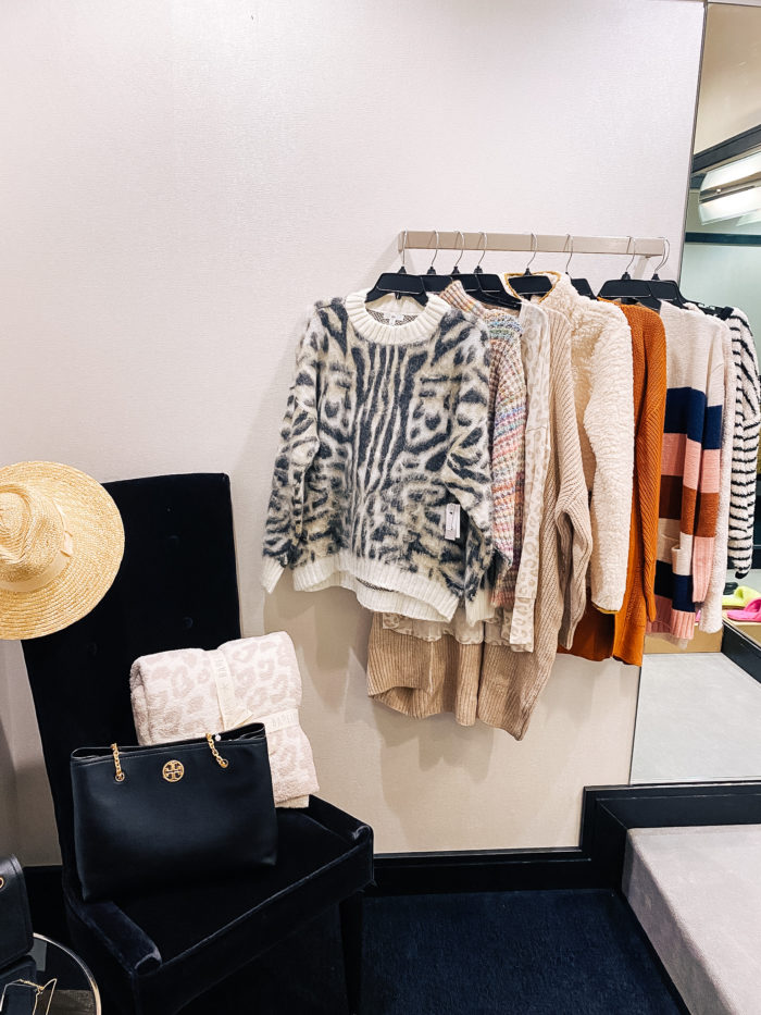 Nordstrom Anniversary Sale by popular Utah fashion blog, A Slice of Style: image of some Nordstrom sweaters hanging on a clothing rack next to a chair with a tory burch bag, Brixton hat, and Barefoot Dreams blanket on it.