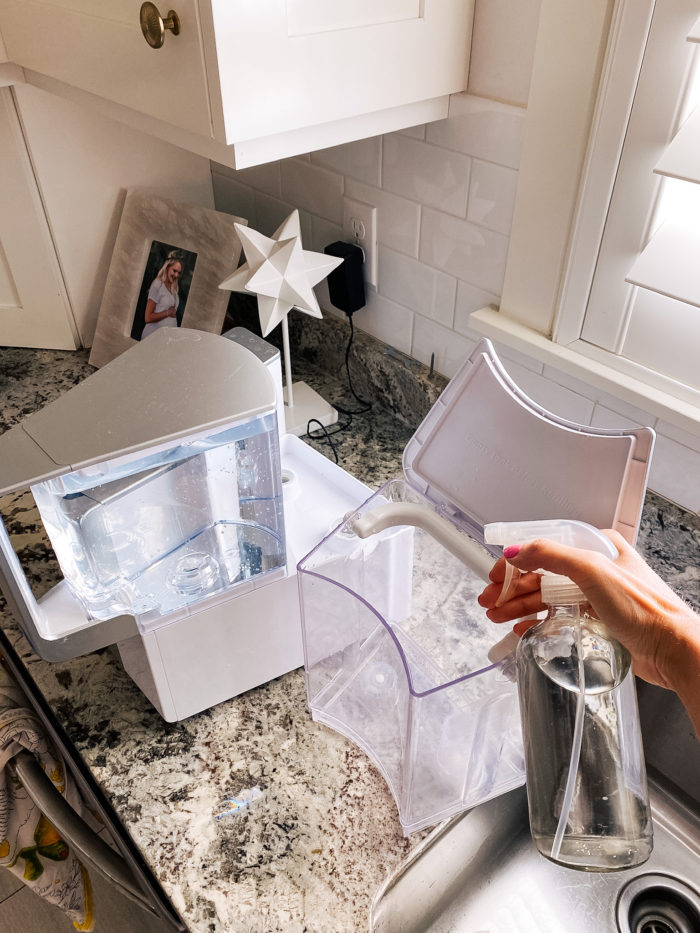 toxin-free home | Branch Basics Reviews by popular Utah lifestyle blog, A Slice of Style: image of Jenica Parcell holding a spray bottle next to her Aqua Tru water purifier.