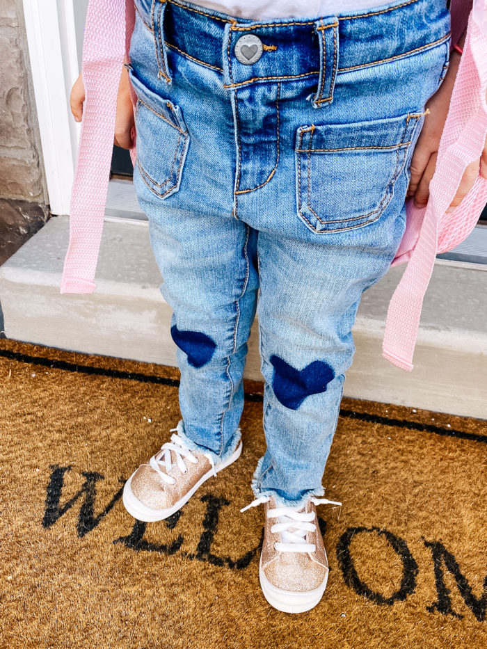 Back to School Checklist by popular Utah motherhood blog, A Slice of Style: image of a young girl wearing a Walmart Wonder Nation Baby Girls & Toddler Girls Heart Knee Patch Jeans, Walmart Wonder Nation Casual Bump Toe Sneaker, Limited Too Girl's Metallic & Glitter Backpack with Lunch Bag and standing on her front porch steps.